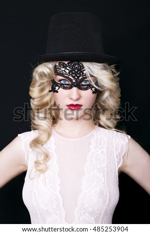 Young gorgeous blonde woman with hat on a dark background