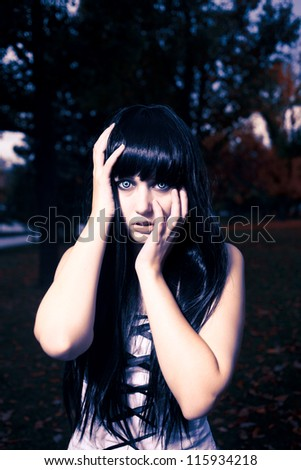 Young gorgeous brunette posing over mysterious Halloween background - stock photo
