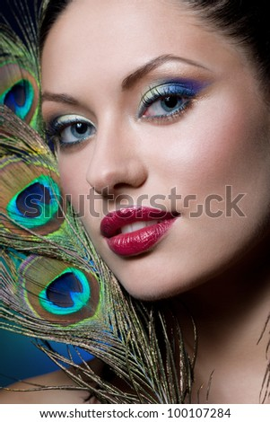 young gorgeous brunette with peacock style makeup, studio shot