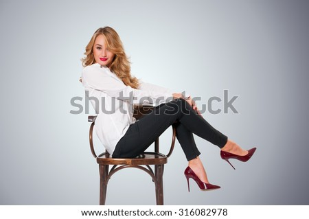 Young gorgeous caucasian blonde sitting and posing on a chair - stock photo