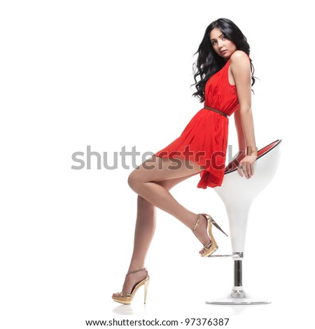 young gorgeous caucasian brunette in red dress on the chair, isolated on white, studio shot - stock photo