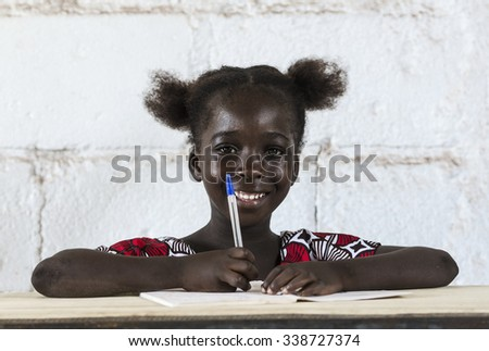 Young gorgeous little schoolgirl at school. Education icon concept for Africa. - stock photo
