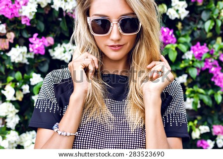 Young gorgeous stunning blonde young woman , wearing stylish outfit, trendy sparkled crop top and sunglasses, posing in floral garden background, beautiful summer day. - stock photo