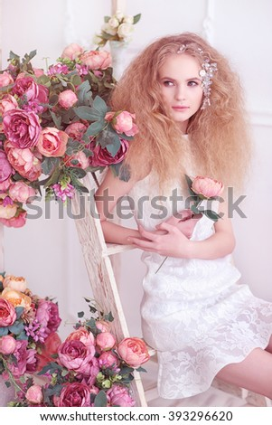 Young gorgeous woman, bride, blond long curly hair, studio decoration, white dress, flowers, soft colours - stock photo