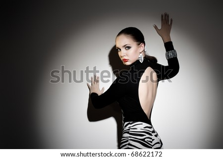 young gorgeous woman posing against the wall, dramatic lighting