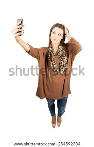 Young gorgeous woman taking self portrait or selfie with smartphone.  Full body length portrait isolated over white background. - stock photo