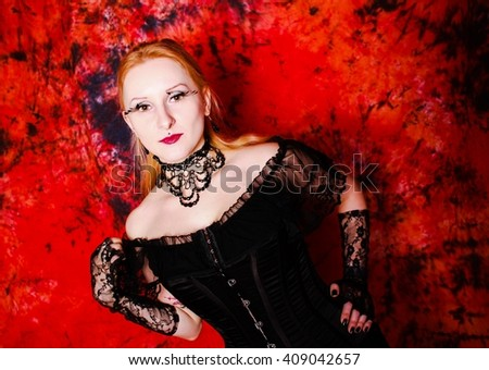 Young gothic woman in the dark gloomy room