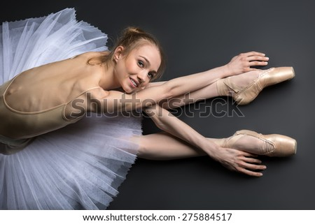 Young, graceful ballerina sitting on the floor on a black background in a studio in the slope face touching knees.