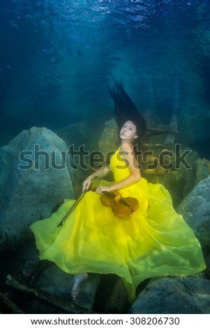 Young graceful woman in a dress posing near the stairs in the lake - stock photo