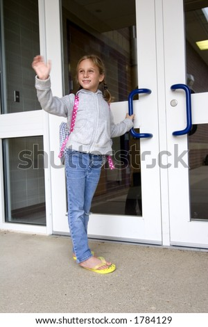 Young grade school age girl waves as she heads off to school - stock photo
