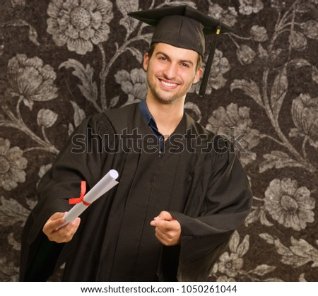 Young Graduation Man Holding Certificate On Wallpaper