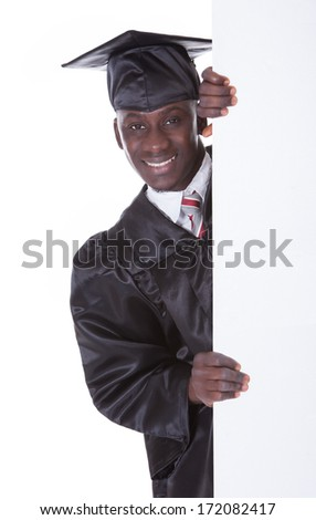 Young Graduation Man Holding Empty Billboard Over White Background
