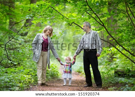 Young grandparents walking with their baby granddaughter in a park in autumn - stock photo