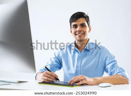 Young graphic designer sitting at desk and working