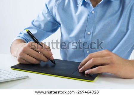 Young graphic designer sitting at desk and working - stock photo