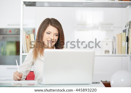 Young graphic designer working on laptop using tablet at home. - stock photo