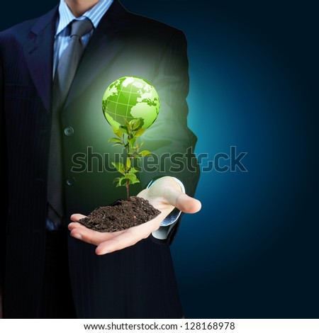 Young green plant in the hand of a businessman Elements of this image furnished by NASA. - stock photo
