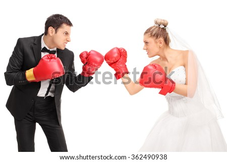 Young groom and a bride fighting each other with boxing gloves isolated on white background - stock photo