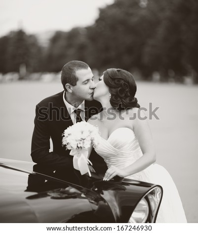 Young groom and bride at field. Wedding couple together in black and white.