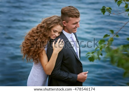 young groom and bride hugging on the background of lake