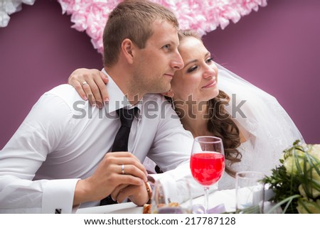 young groom and bride  in restaurant sit by banquet table - stock photo