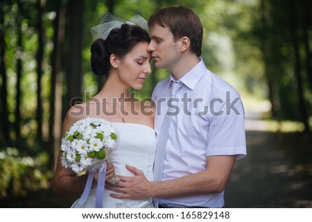Young groom and bride portrait outdoors. Shallow depth of field - stock photo