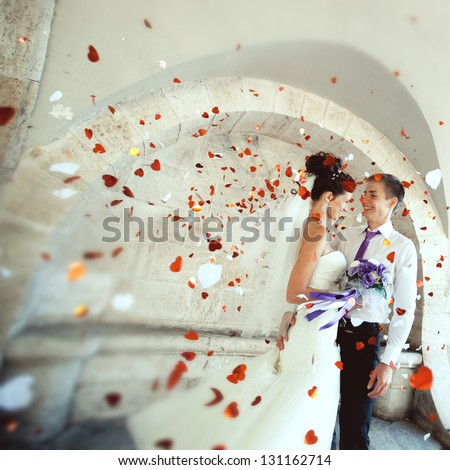young groom embraces the bride at the festival, everyone is happy, flying confetti. Wedding festive theme - stock photo