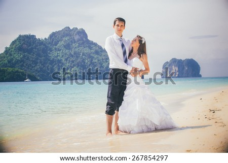 young groom hold his brunette bride standing on sandy beach against azure sea and rocky island