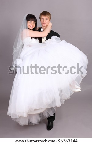 Young groom holds beautiful bride in studio on gray background - stock photo