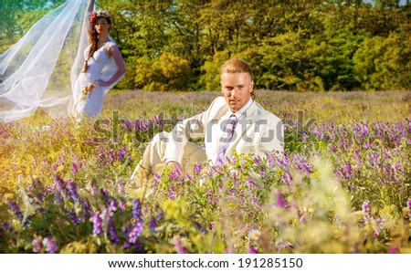 young groom in a white suit against the bride and the nature