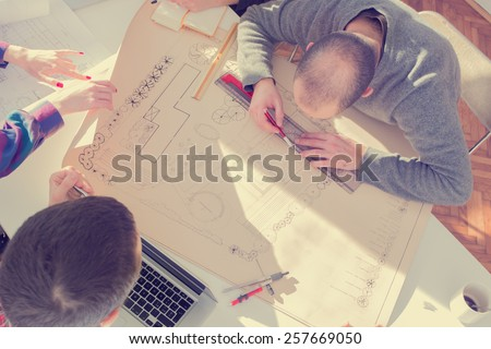 Young group of architects discussing business plans in a natural lit office. - stock photo