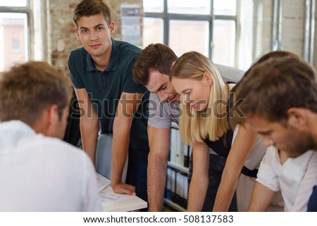 Young group of businesspeople in an informal meeting gathered around a woman at a desk discussing paperwork with focus to the businessman