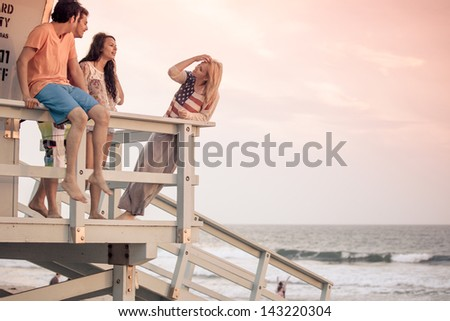 Young Group of Friends at the Beach on the Lifeguard stand in Southern California - stock photo