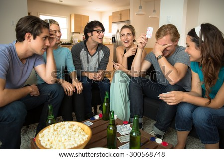 Young group of friends attractive people laughing embarrassed poker player card game night loser winner - stock photo