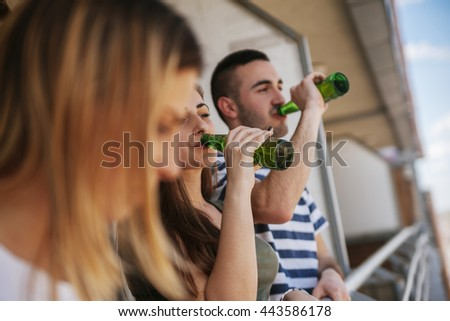 Young Group Of Friends On A Balcony Drinking Beer - stock photo