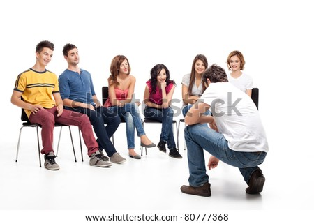young group of friends, sitting down, listening to man showing - stock photo