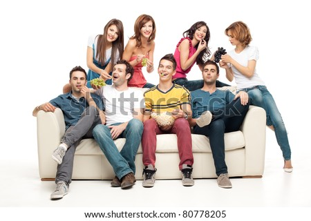 young group of friends sitting on couch eating - stock photo