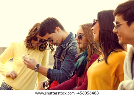 Young group of friends with smart phones outdoors - stock photo