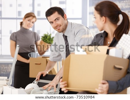 Young group of office workers moving to new office, unpacking boxes, smiling.
