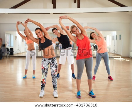 Young group of people training stretching exercises in gym - stock photo