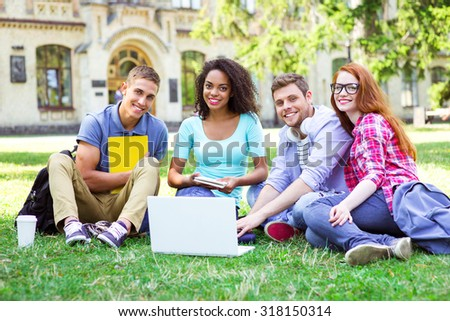 Young group of students with backpacks and books smiling, sitting on grass and using laptop. Campus as a background - stock photo