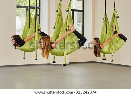 Young group women making antigravity yoga exercises. green hammocks.