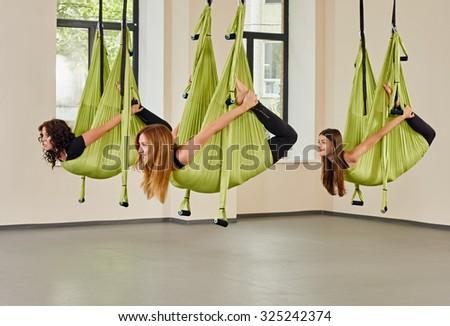 Young group women making antigravity yoga exercises. green hammocks.  - stock photo