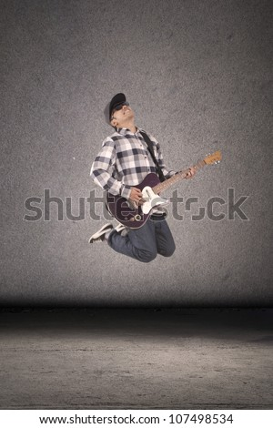 Young guitar player perform at street jumping in front of dark background - stock photo