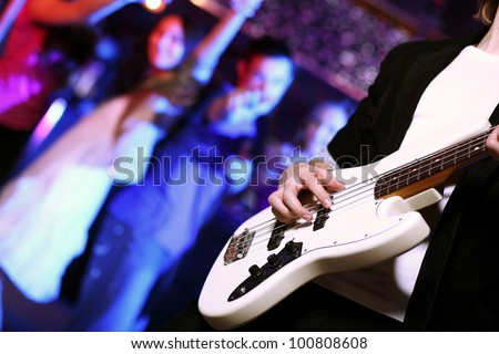 Young guitar player with instrument performing in night club