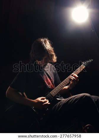 young guitarist play on the electric guitar - stock photo