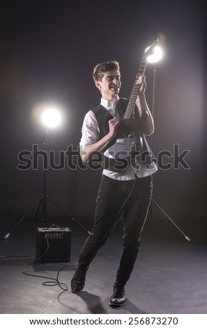 Young guitarist with the electric guitar, isolated on dark background.