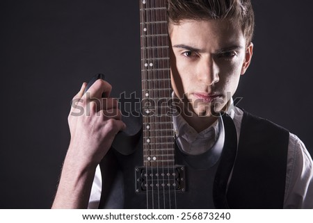 Young guitarist with the electric guitar, isolated on dark background is looking at the camera. - stock photo