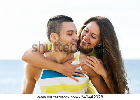 Young  guy and beautiful girl  spending free time at seaside in sunny day - stock photo