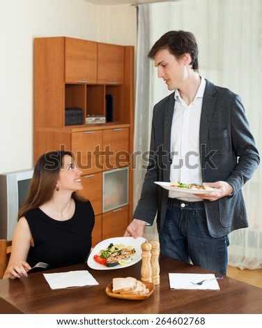 Young guy and girl  having romantic dinner with wine  in home interior - stock photo